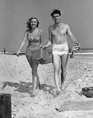 Vintage couple walking on beach for picnic.