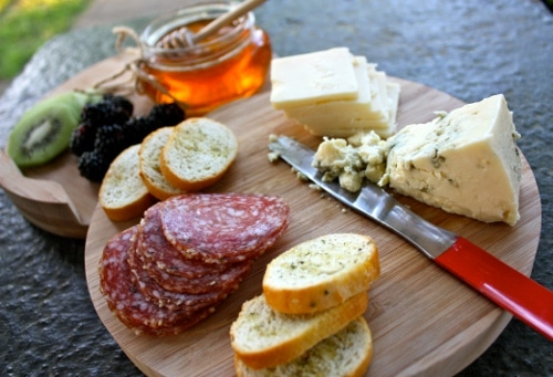 Cheese board of food items with knife.