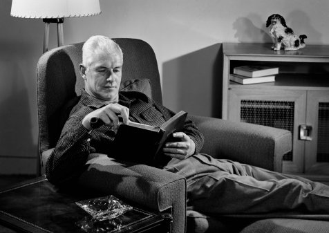 Vintage man sitting on chair and reading book.