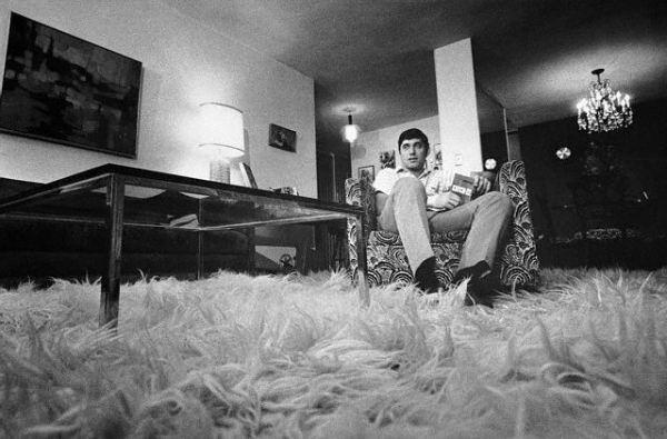 Joe Namath sitting on shag fluffy rug in living room.