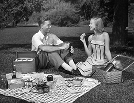 Vintage couple enjoying picnic at outside.