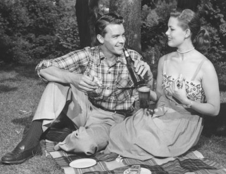 Vintage couple drinking beer on picnic.