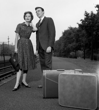 Vintage couple standing near train tracks with luggage.