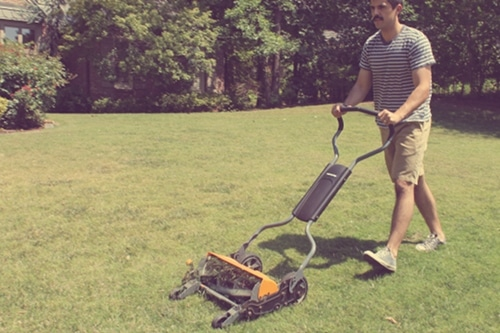 Vintage man mowing with Fiskars push peel illustration.