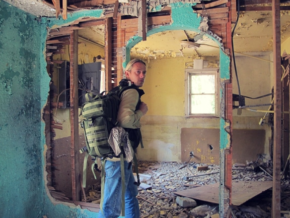 Man carrying backpack and visiting an old house.