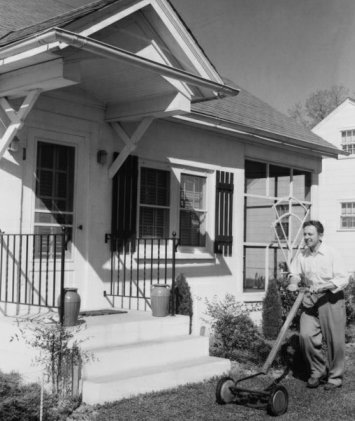 Vintage man pushing reel mover front of a house.