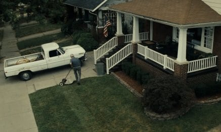 Vintage man pushing reel mower and a vehicle front of a house.