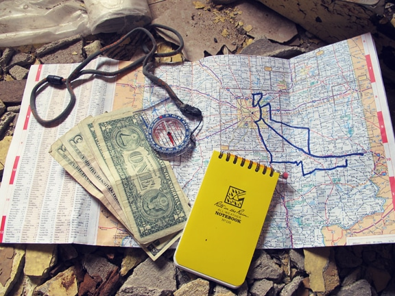 Money and notebook placed on map.