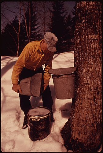 Man pouring water into bucket in cold weather.