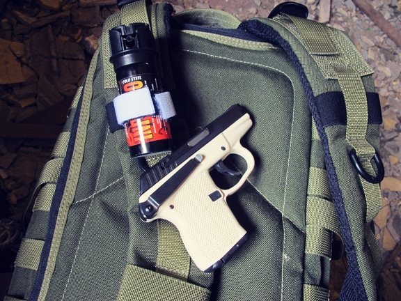 Pepper spray and pistol placed on survival bag.