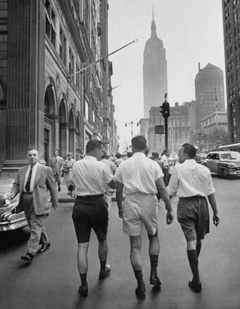 Men wearing shorts walking down the street.