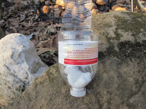 Vintage crude water filter placed at the stones.