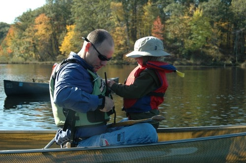 Man enjoying canoeing in lake with son.