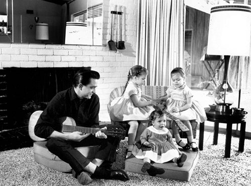 Vintage a man sitting with three little children's and playing guitar.