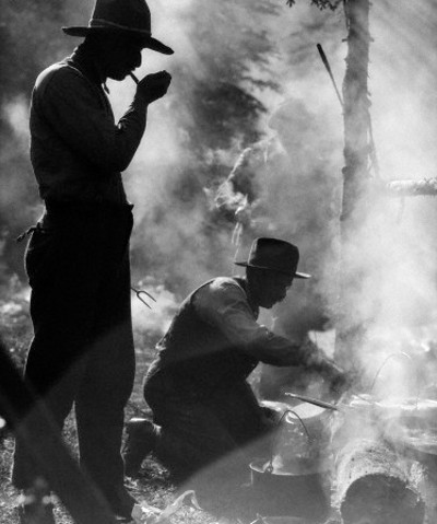 Vintage cowboys men outdoors cooking cast iron fire.