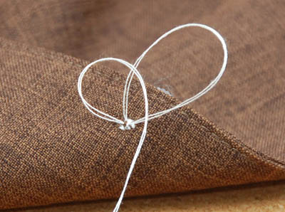 sew a button tying off back end close up
