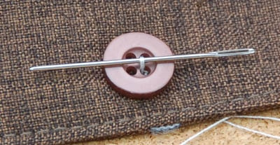 Needle attached with button by white thread.