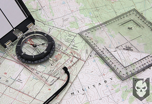 Compass lying on topographic maps.