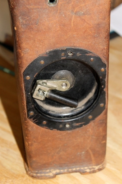 Vintage removing the screws from the crank handle on the side.