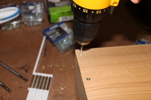Vintage drilling pilot holes before screwing in the screws.