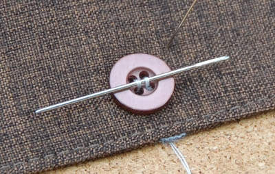 Button attached to a cloth by thread and needle.