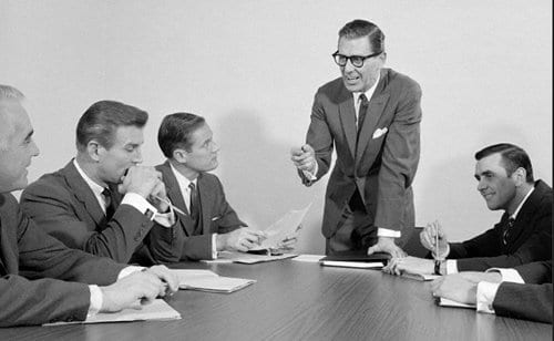 Vintage man giving presentation in office meeting.