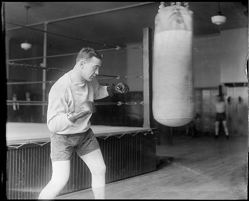 vintage man amateur boxer punching heavy bag