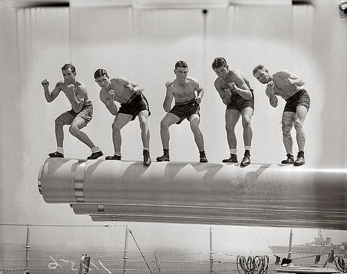 Vintage sailors boxers standing on ship guns.