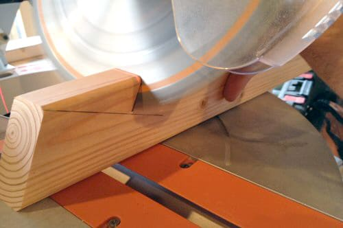 cutting wood board with miter saw action shot close up