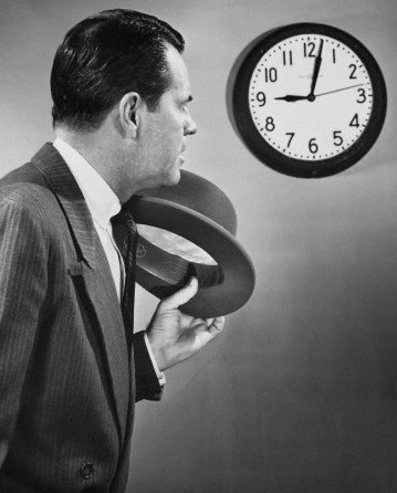 vintage man businessman hat off looking at clock