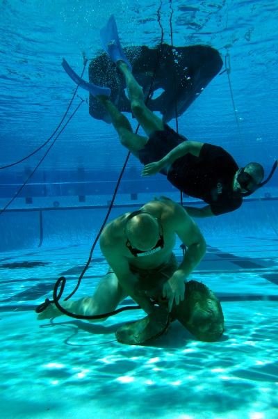 Navy seals under water tying knots pool training.