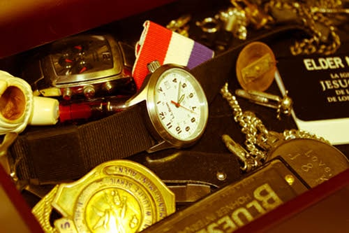 Vintage treasure box watches and coins placed at table.
