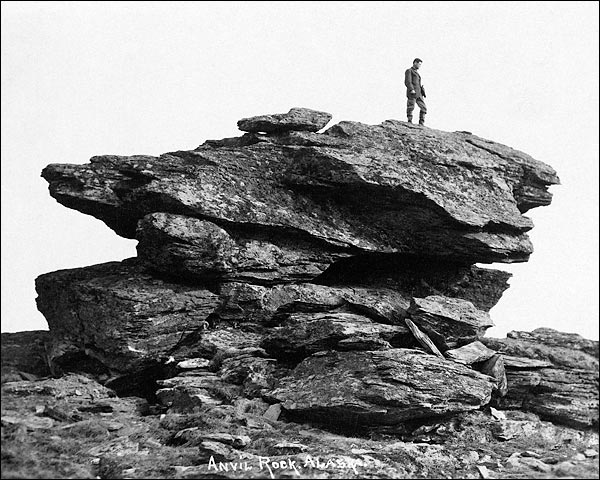 Vintage man standing on large anvil rock alaska.