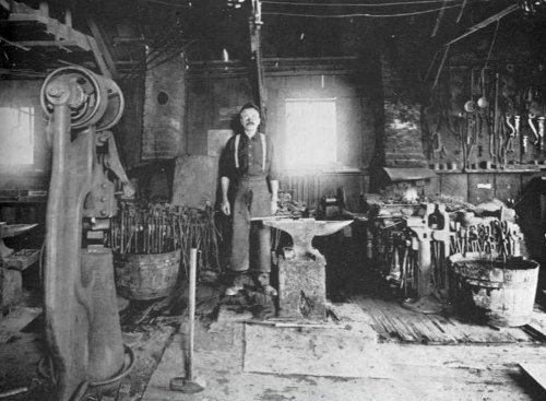 vintage man blacksmith in shop behind anvil