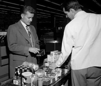vintage man at grocery store counter paying for food