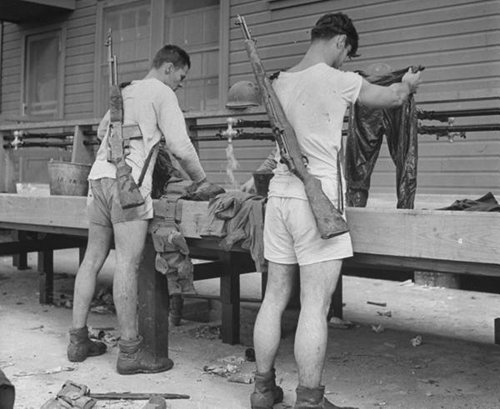 vintage military men in underwear doing laundry with guns