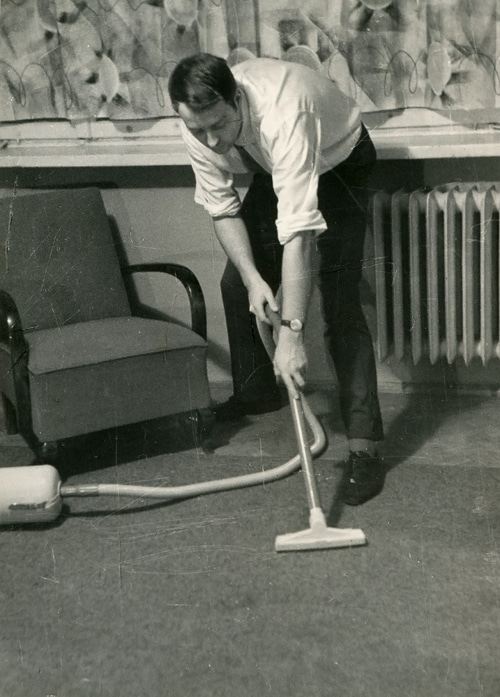 vintage man vacuuming floor business clothes
