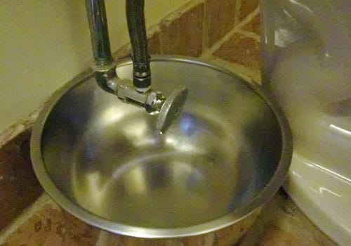 draining water tank of toilet bowl into basin