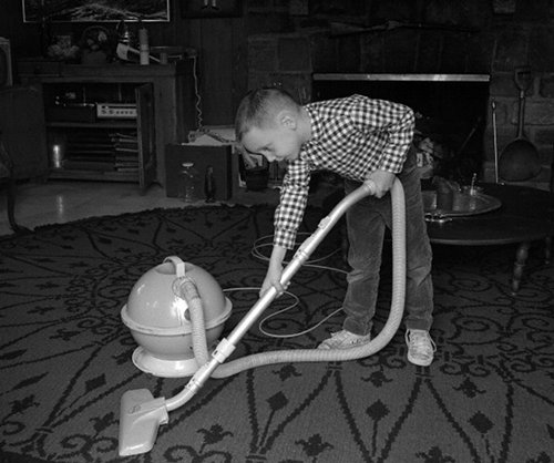 Vintage young boy vacuuming floor doing chores.