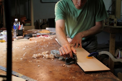 luthier guitar maker working on making instrument