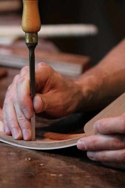 Luthier guitar maker working on curved wooden panel.