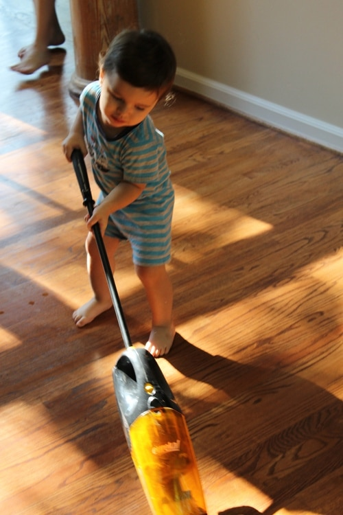 young boy doing chores vacuuming floor