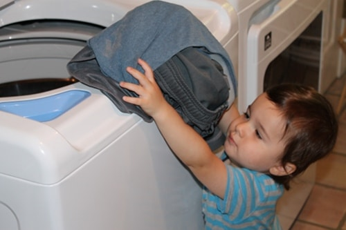 young boy putting clothes laundry in washer doing chores