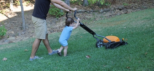 young boy helping dad mow lawn