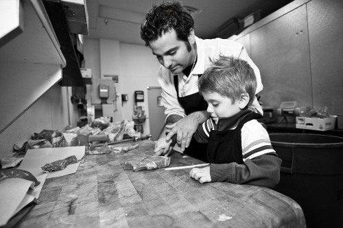 Danny Catullo butcher showing young boy how to cut meat.