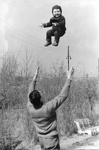 Vintage dad throwing son baby high into air.