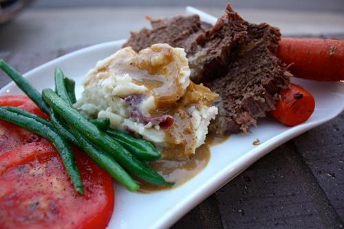 Meat potatoes gravy green beans carrots on plate.