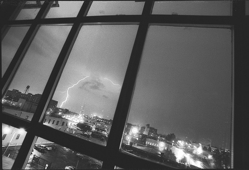 lightning strike from storm looking out window over city