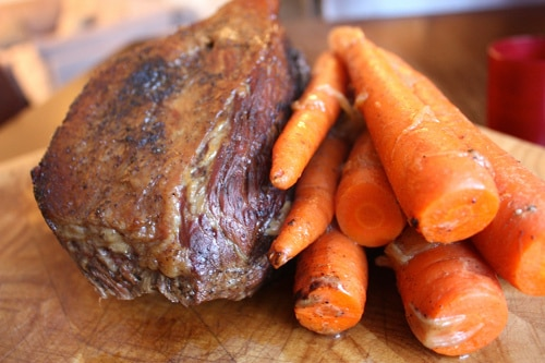 Roast beef and carrots cooked on cutting board.