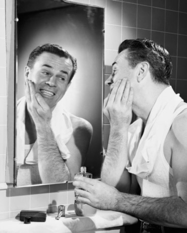 vintage man looking in mirror after shave smiling
